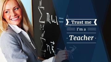 Female teacher writing on chalkboard