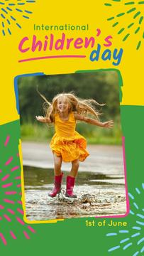 Happy girl jumping in the puddle on Children's Day